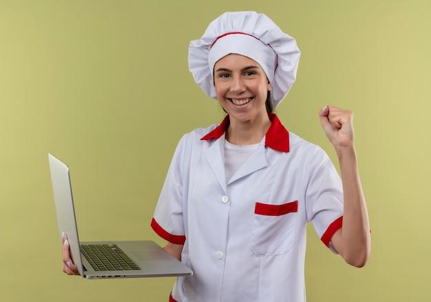 Het jonge glimlachende kaukasische kokmeisje in eenvormige chef-kok houdt laptop en heft vuist op die op groene achtergrond met exemplaarruimte wordt geïsoleerd