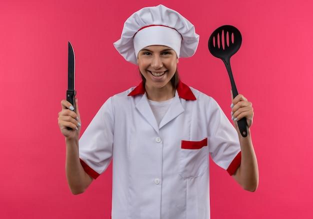 Het jonge glimlachende kaukasische kokmeisje in eenvormige chef-kok houdt mes en spatel die op roze ruimte met exemplaarruimte wordt geïsoleerd