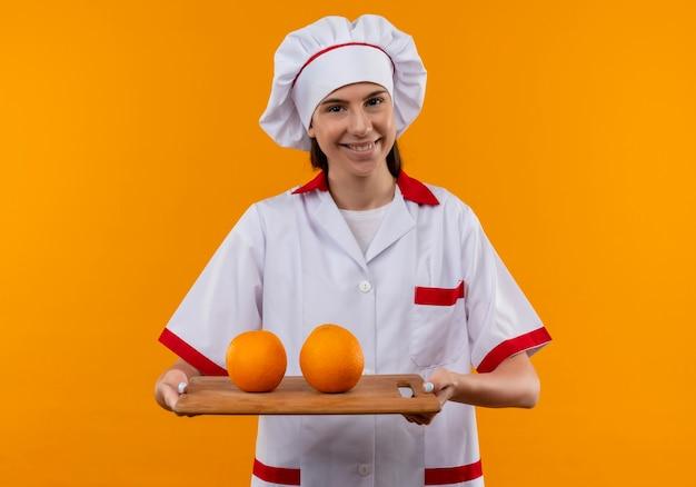 Het jonge glimlachende kaukasische kokmeisje in eenvormige chef-kok houdt sinaasappelen op scherpe raad die op oranje ruimte met exemplaarruimte wordt geïsoleerd
