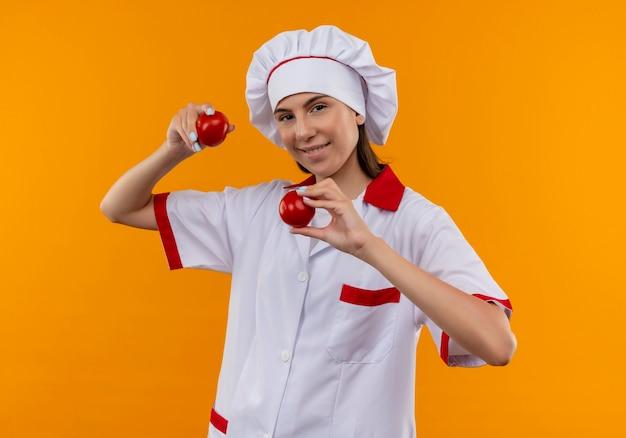 Het jonge glimlachende kaukasische kokmeisje in eenvormige chef-kok houdt tomaten die op oranje achtergrond met exemplaarruimte worden geïsoleerd