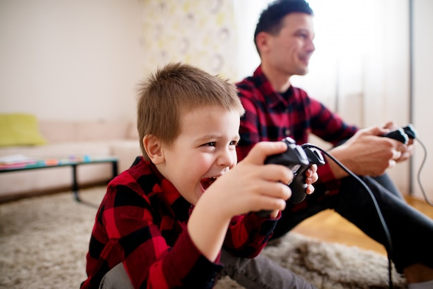 Het jonge glimlachende kind beraamt hoe hij zijn vader in consolespel moet verslaan terwijl hij een gamepad vasthoudt en op de vloer zit.