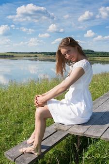 Het jonge glimlachende meisje in witte kleding is op houten lijst, en bekijkt camera op de achtergrond van het rivierlandschap in de zomer.
