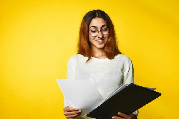 Het jonge glimlachende meisje kijkt in de documenten