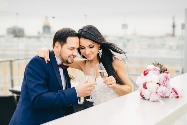 Het jonge hartelijke paar in de glazen van het liefdegerinkel met champagne, omhelst elkaar als viert hun huwelijk