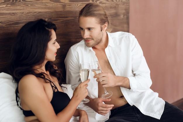 Het jonge hartstochtelijke paar juicht met glazen champagne toe.