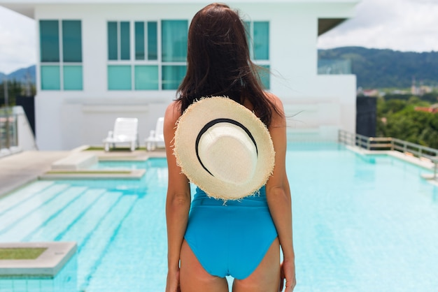 Het jonge heldere donkerbruine vrouwen blauwe zwempak ontspannen