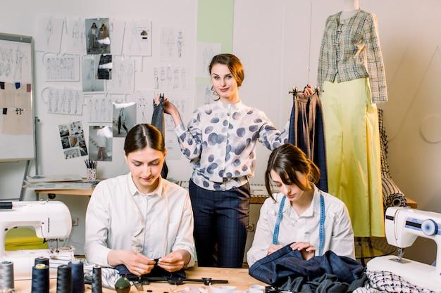 Het jonge het glimlachen manierontwerper stellen met met de hand gemaakte broek op hangers bij naaiatelier en het bekijken camera. twee mooie naaisters naaien in hun atelier. naaister aan het werk