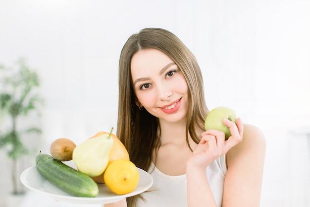 Het jonge het glimlachen vruchten van de vrouwenholding assortiment diende op witte plaat en groene appel tegen lichte achtergrond.