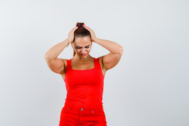 Het jonge hoofd van de vrouwenholding met handen, neerkijkend in rood mouwloos onderhemd, broek en op zoek pijnlijk, vooraanzicht.