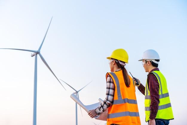 Het jonge ingenieursteam analyseert een blauwdruktekening van windturbinepark