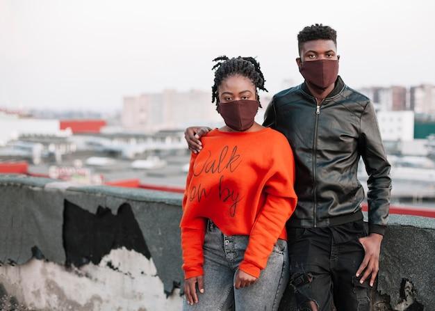 Het jonge jongen en meisjes stellen met gezichtsmaskers