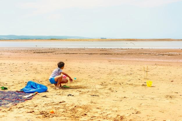 Het jonge jongen spelen met zand op het strand op een zonnige dag