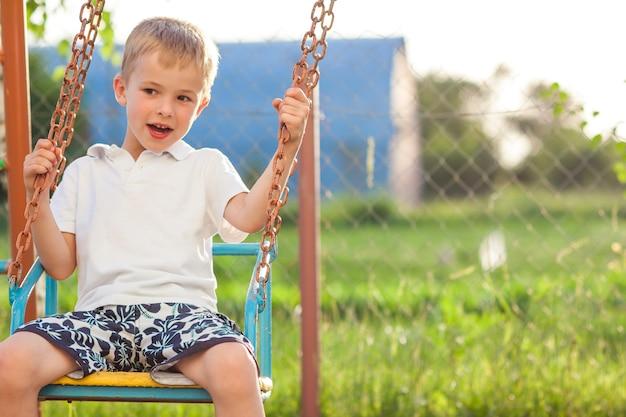 Het jonge jongen spelen op schommeling in zonnige de zomerdag