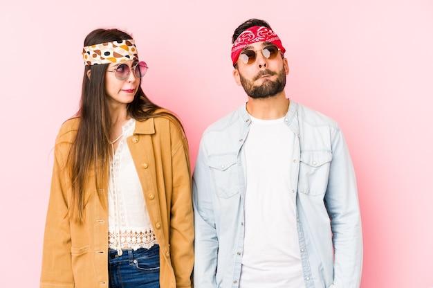 Het jonge kaukasisch paar dat de kleren van een muziekfestival draagt geïsoleerd verward, voelt twijfelachtig en onzeker.