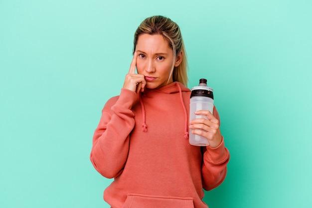 Het jonge kaukasische drinkwater van de sportvrouw dat op bluepointing tempel met vinger wordt geïsoleerd, denken, gericht op een taak.