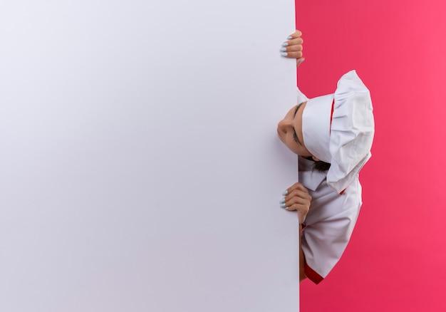 Het jonge kaukasische kokmeisje in eenvormige chef-kok bevindt zich achter en bekijkt witte muur op roze met exemplaarruimte