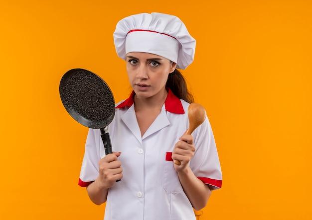 Het jonge kaukasische kokmeisje in eenvormige chef-kok houdt koekenpan en houten lepel die op oranje achtergrond met exemplaarruimte wordt geïsoleerd