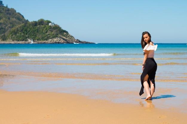 Het jonge kaukasische meisje stellen bij de baai van la concha in baskenland donostia-san sebastian.