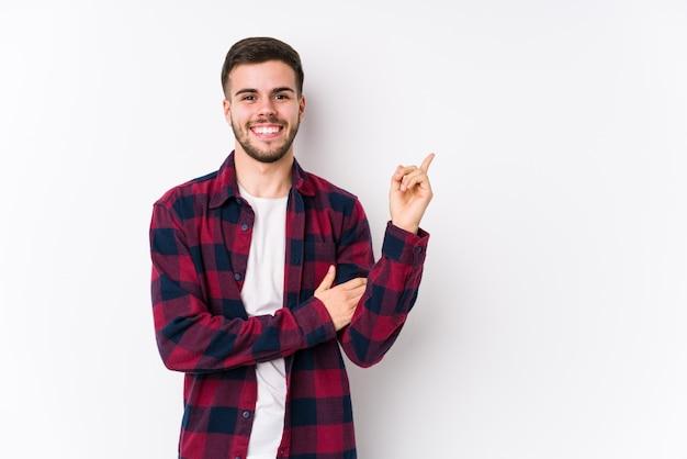 Het jonge kaukasische mens stellen in een witte muur isoleerde het glimlachen vrolijk wijzend met weg wijsvinger.