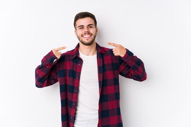Het jonge kaukasische mens stellen in het witte muur glimlachen, die vingers op mond richten.