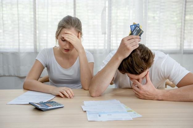 Het jonge kaukasische ongerust gemaakte paar heeft hulp nodig in de bank van de spanning thuis bankboekhouding schuldenrekeningen bank papieren uitgaven en betalingen voelen zich wanhopig in slechte financiële situatie en faillissement.