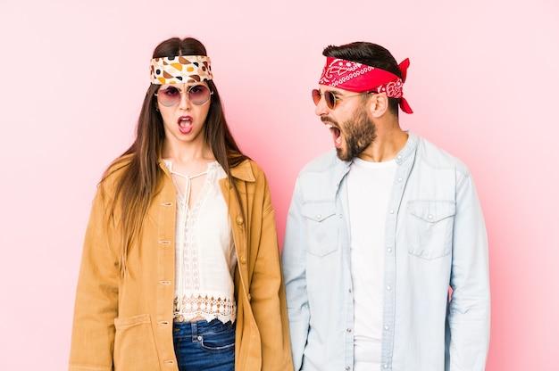 Het jonge kaukasische paar die een muziekfestival dragen kleedt zeer boos en agressief gillen.