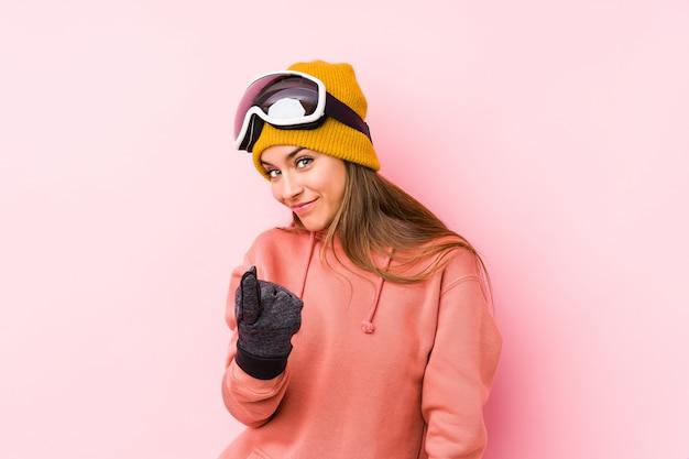 Het jonge kaukasische vrouw dragen geïsoleerde ski kleedt het richten met vinger op u alsof uitnodigend dichter komt.