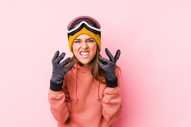 Het jonge kaukasische vrouw dragen geïsoleerde ski kleedt het verstoorde gillen met gespannen handen.