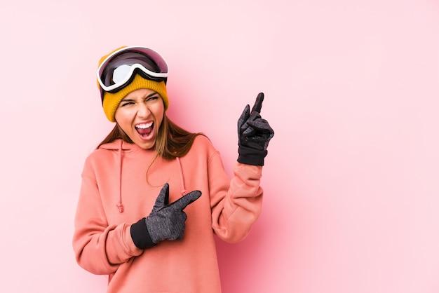 Het jonge kaukasische vrouw dragen ski kleedt geïsoleerde het richten met wijsvingers aan een exemplaarruimte, die opwinding en wens uitdrukken.