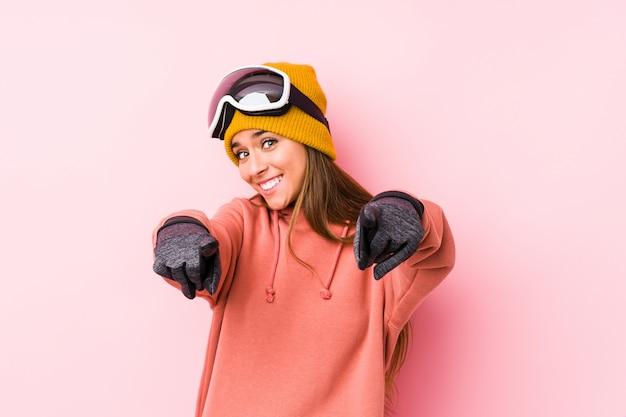 Het jonge kaukasische vrouw dragen ski kleedt geïsoleerde vrolijke glimlachen die aan voorzijde richten.