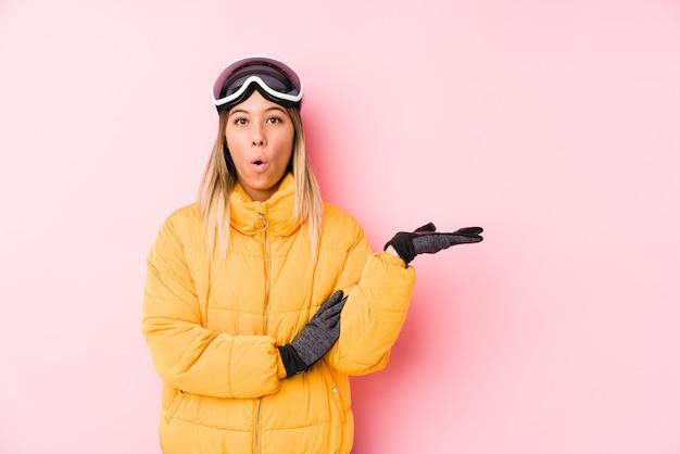 Het jonge kaukasische vrouw dragen ski kleedt zich in een roze muur onder de indruk het exemplaarruimte van de holding op palm.