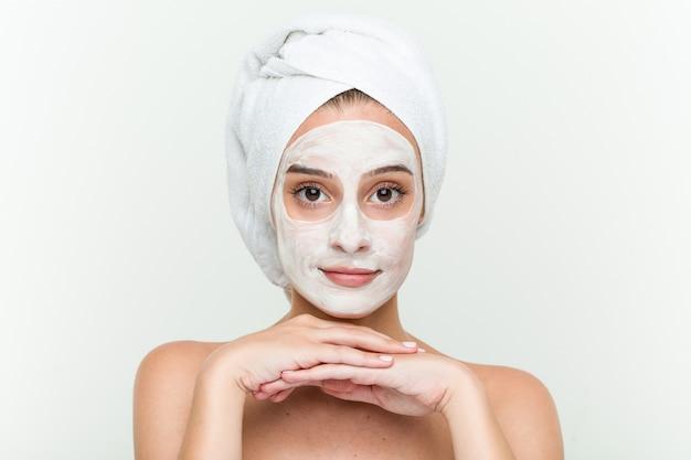 Het jonge kaukasische vrouw genieten van van een gezichtsmaskerbehandeling