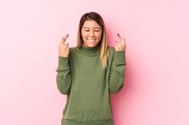 Het jonge kaukasische vrouw stellen die vingers kruisen voor het hebben van geluk