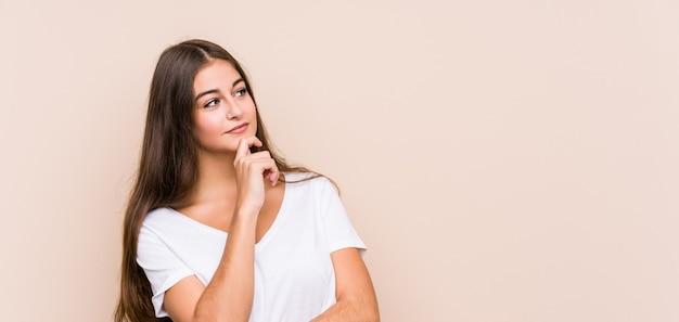 Het jonge kaukasische vrouw stellen geïsoleerd zijwaarts met twijfelachtige en sceptische uitdrukking op zoek.