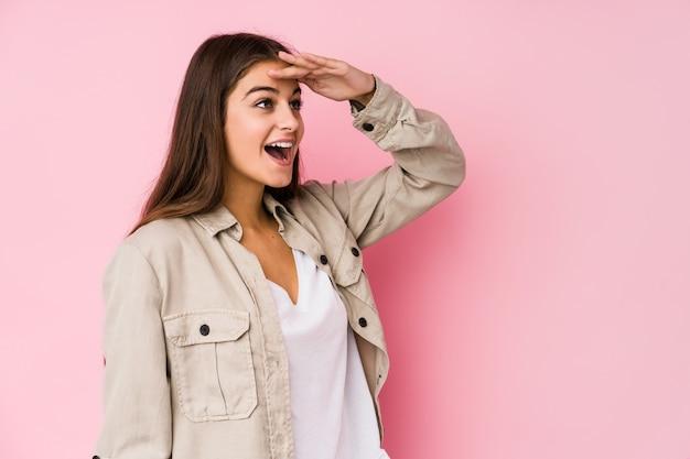 Het jonge kaukasische vrouw stellen in een roze muur die ver weg houdend hand op voorhoofd kijken.