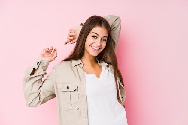 Het jonge kaukasische vrouw stellen in roze muur het uitrekken zich wapens, ontspannen positie.