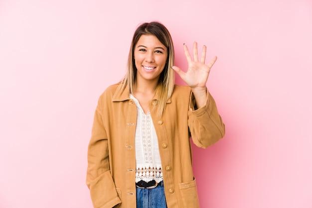 Het jonge kaukasische vrouw stellen isoleerde glimlachend vrolijk tonend nummer vijf met vingers.
