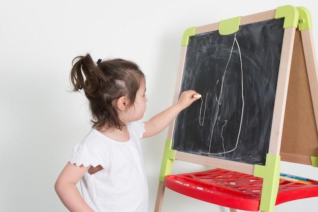Het jonge kindmeisje maakt een krijttekening