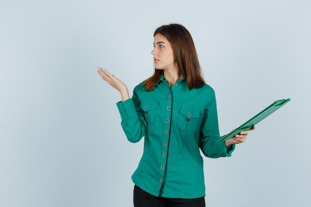 Het jonge klembord van de meisjesholding, die palm opzij spreidt, naar linkerkant in groene blouse, zwarte broek kijkt en ernstig kijkt. vooraanzicht.