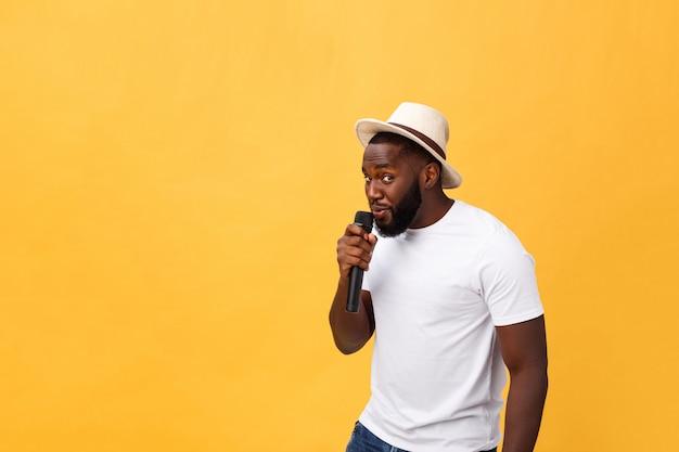 Het jonge knappe afrikaanse amerikaanse jongen zingen emotioneel met microfoon die op gele achtergrond wordt geïsoleerd