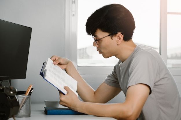 Het jonge knappe aziatische boek van de mensenlezing bij het werkbureau in vrije tijd van thuis het werken, kennis en het leren concept