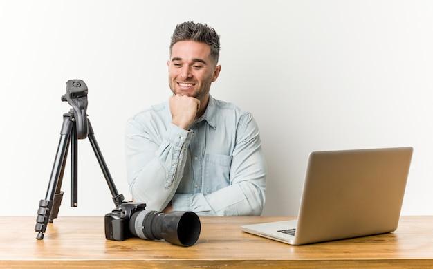 Het jonge knappe fotografieleraar gelukkig en zeker glimlachen, wat betreft kin met hand.