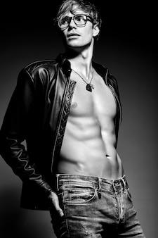 Het jonge knappe gespierde geschikte mannelijke modelmens stellen in studio die zijn buikspieren in leerjasje toont