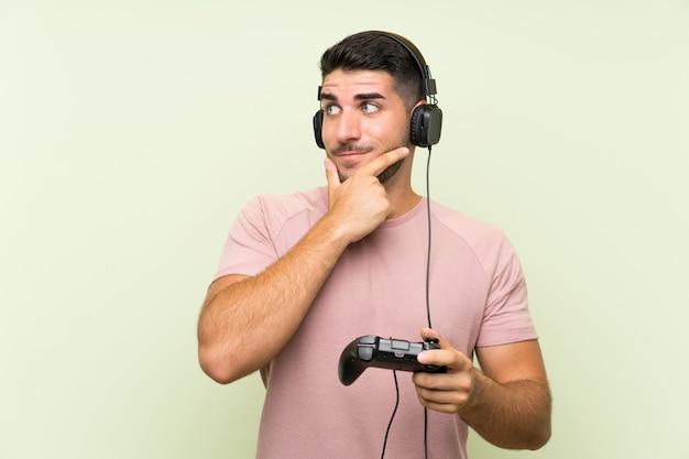 Het jonge knappe mens spelen met een videospelletjecontrolemechanisme over geïsoleerde groene muur die een idee denken