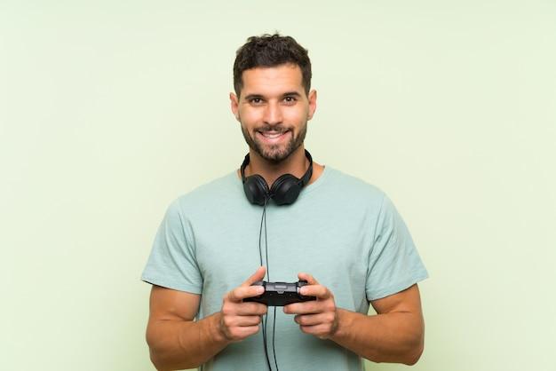 Het jonge knappe mens spelen met een videospelletjecontrolemechanisme over geïsoleerde groene muur die heel wat glimlacht