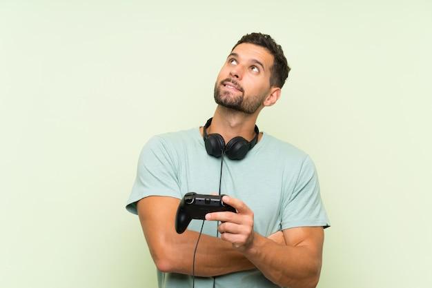 Het jonge knappe mens spelen met een videospelletjecontrolemechanisme over geïsoleerde groene muur die omhoog terwijl het glimlachen kijken
