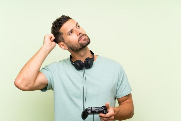 Het jonge knappe mens spelen met een videospelletjecontrolemechanisme over geïsoleerde groene muur die twijfels hebben en met verwarren gezichtsuitdrukking