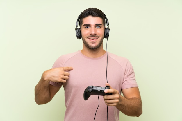 Het jonge knappe mens spelen met een videospelletjecontrolemechanisme over geïsoleerde groene muur met verrassingsgelaatsuitdrukking