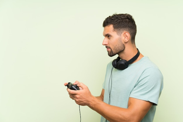 Het jonge knappe mens spelen met een videospelletjecontrolemechanisme over geïsoleerde groene muur