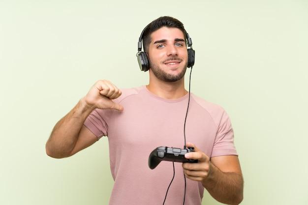Het jonge knappe mens spelen met een videospelletjecontrolemechanisme over geïsoleerde groene trots en zelf tevreden muur